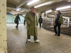 Man in the Subway (UrbanphotoZ) Tags: nyc newyorkcity ny newyork man hat cane walking subway pedestrian sneakers midtown trenchcoat timessquare passenger westside glassbricks passageway 42st