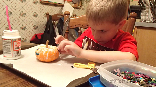 decorating a mini pumpkin for halloween