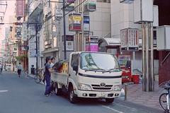 Deliveries (JanneM) Tags: street film japan truck 35mm canon eos kiss kodak jan 400 大阪 delivery 日本 osaka namba kansai portra shinsaibashi platser janne 関西 難波 objekt moren människor händelser importerataggar
