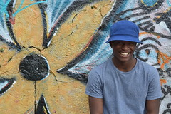 'Cheesin' (miranda.valenti12) Tags: flowers light portrait flower colors smile hat smiling wall graffiti expression background facial foreground cheesing tyree
