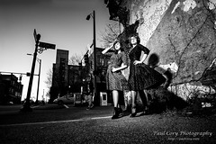 Ladies, with Bystander B&W (Paul Cory) Tags: lighting camera city winter sunset sky people urban blackandwhite woman building tree crimson fashion female buildings season lens model unitedstates northcarolina bluesky structure greensboro softbox onlocation strobe citystreet geolocation postprocessing fujicamera alienskin timeofday modifiers downtowngreensboro niksoftware exif:make=fujifilm camera:make=fujifilm lumiquestsoftboxiii exif:aperture=80 exposurex colorefexpro4 zeisstouit12mmf28 dianacameronmcqueen exif:lens=touit2812 fujifilmxt1 exif:isospeed=400 exif:focallength=12mm camera:model=xt1 exif:model=xt1 godoxv850 zeisstouitlens