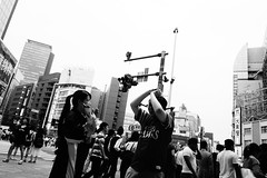 Swinging an imaginary bat (halskygene) Tags: road street city light urban sun white man black girl monochrome japan asian photography japanese tokyo fan photo shinjuku asia cityscape traffic bright baseball cloudy bat talk