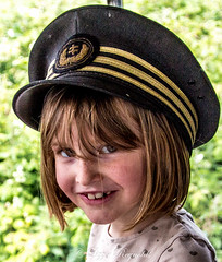Day 187, 2016, a photo a day. (lizzieisdizzy) Tags: outside outdoors child girl female smile grin smiling teeth eyes shining fairhaired pretty adorable hat cap railwaycap cheeky fringe window depthoffield laughing grinning happy