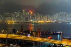 Safe From A Distance (Tim van Zundert) Tags: china road city light sea reflection water skyline architecture night zeiss buildings point boats island evening construction asia long exposure cityscape crane sony towers north hong kong 55mm pollution kowloon a7r sel55f18z
