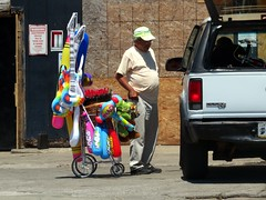 A senior citizen selling WHACK hammers and POW bats. (kennethkonica) Tags: life street old city summer people urban usa signs men hat sign america work canon glasses midwest sitting shadows random outdoor candid indianapolis seat wheels working streetphotography indy indiana cardboard mature sit vendor persons seated selling economy alternative global canonpowershot hoosier marioncounty seniorcitizen presidentobama