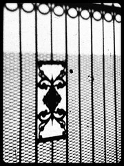 Shadowgate (catheadsix) Tags: orcafilter flickriosapp:filter=orca uploaded:by=flickrmobile gate bw shadow sunny street walk ombre portail