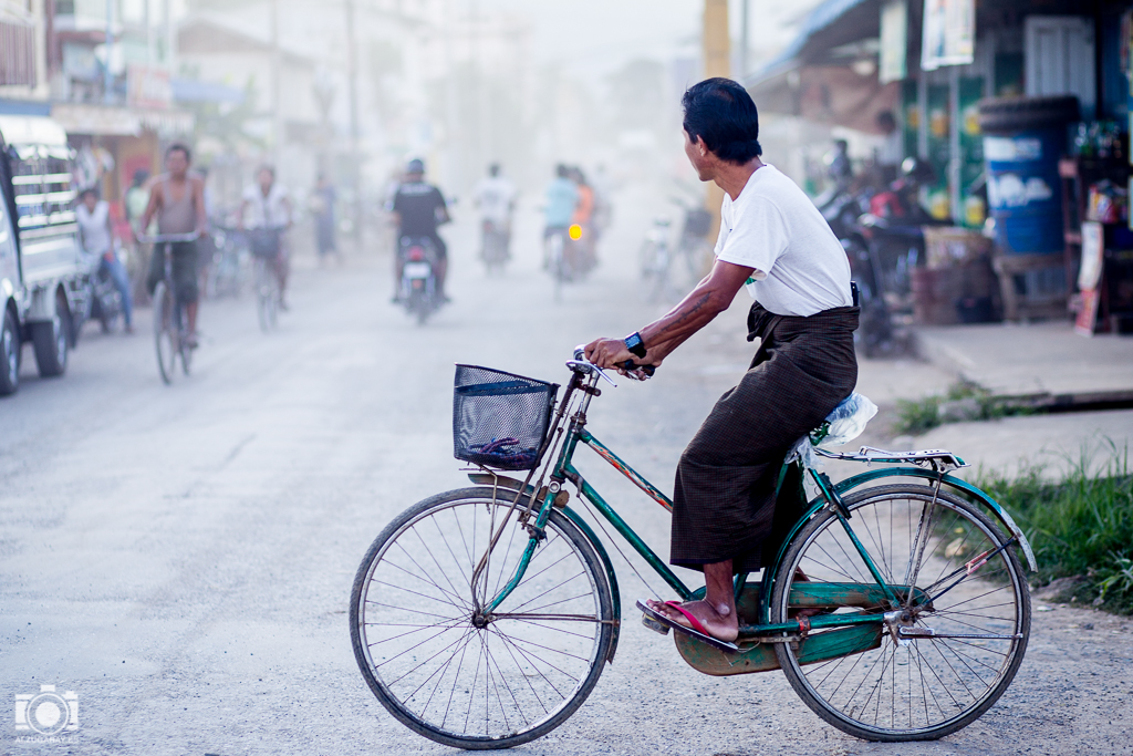 Hombre montado en bicicleta observa el tráfico de Nyaungshwe
