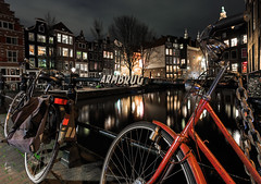 Night Parking (McQuaide Photography) Tags: city longexposure nightphotography travel bridge light red urban house holland reflection tourism window water netherlands amsterdam bike bicycle architecture night photoshop canon eos evening licht canal europe dof nacht availablelight parking tripod transport nederland wideangle depthoffield parked brug fullframe dslr avond redlight residential redlightdistrict 1740mm stad stationary rld fiets manfrotto noordholland gracht lightroom 6d wideanglelens lseries 17mm northholland famousplace groothoek traveldestination canon6d armbrug mcquaidephotography