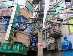"""Seoul Korea backalley near Dongmyo flea market draped in wires - """"Seoul is a very wired city"""" (moreska) Tags: travel urban signs tourism walking asia backalley cityscapes korea cables wires seoul messy hanging cramped clutter rok packed crowded tangled cityscenes signboards muddle tangly visualoverload"""