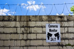 24/7 (Chris B Richmond) Tags: camera blue sky brick wall clouds canon fence outside big wire tn nashville outdoor brother tennessee surveillance text monitor cameras lettering dslr barbed 247