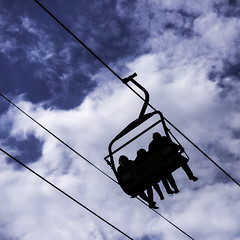Three On A Chair Lift (Mabry Campbell) Tags: blue sky people usa up silhouette clouds photography march photo texas photographer unitedstates image tx unitedstatesofamerica houston 85mm photograph 100 squarecrop chairlift fineartphotography architecturalphotography 2015 commercialphotography f32 ef85mmf18usm houstonlivestockshowrodeo architecturephotography fineartphotographer sec mabrycampbell march152015 20150315h6a4321