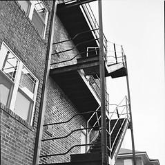 escape! (GJosephT) Tags: building 120 6x6 film monochrome architecture stairs analog zeiss apartment bricks hasselblad developer fireescape medium format ilford fp4 streetview backdoor planar 500cm ddx 80c ilfotec