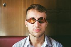 through the orange glass (sympheria) Tags: trip portrait orange man glass smile face train swimming friend gogless