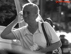 Tissue Vender (Halcon122) Tags: madrid street portrait urban bw woman walking 50mm spain raw alone afternoon candid streetphotography stranger elderly intersection vendor salamanca epm2