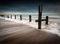 Rushing [Explored] (jellyfire) Tags: longexposure blue sea england sky water sunrise canon landscape dawn sand rocks unitedkingdom norfolk unusual lowkey emotive atmospheric eastanglia groynes happisburgh polariser canon5dmkii zeissdistagont18mmf35ze