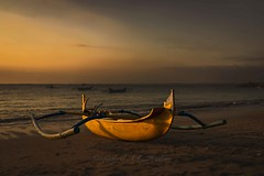 Fishing boat with stabilizers (Syahrel Azha Hashim) Tags: ocean travel light sunset vacation bali holiday detail beach colors clouds 35mm indonesia prime boat colorful waves dof outdoor getaway sony details horizon naturallight nopeople transportation handheld shallow simple fishingboat dramaticsky kuta kutabeach 2015 a7ii colorimage stabilizers sonya7 syahrel ilce7m2