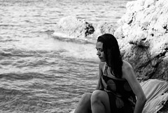 girl sitting on rocks after swimming (gorbot.) Tags: sea summer beach swimming naturereserve sicily roberta canoneos5d riservanaturaledellozingaro silverefex carlzeisszf50mmplanarf14