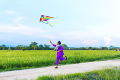 boy playing colorful kite (sydeen) Tags: road morning blue boy sky cloud house kite color green nature field grass one fly flying colorful village play purple offroad paddy walk traditional culture run everning