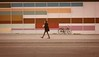 A woman, a wall and a bike (tom_greaves) Tags: road street pink blue red orange woman brown white building geometric lines bike tarmac yellow wall canon copenhagen walking denmark grey pattern straight canon400d rectangales