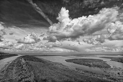 Two Tiny Cyclists In A Big World (Alfred Grupstra Photography) Tags: sky blackandwhite bw water clouds landscape nederland nl dike noordholland denoever