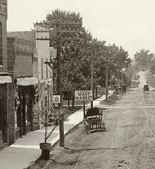 Main Street looking south, Hamilton, Indiana, close-up section 2 (Hoosier Recollections) Tags: people woman usa signs man men history fence buildings advertising awning hardware women hamilton hats bridges indiana streetscene transportation porch drugs shops pedestrians roads storefronts grocery waterpump buggy buggies banks businesses wagons barbers realphoto steubencounty hoosierrecollections