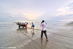 Photographers chase and capture the moment when the fishermen go out to sea (Shahril KHMD) Tags: ocean camera sea industry beach sunrise work walking boat fishing photographer fishermen scene worker moment