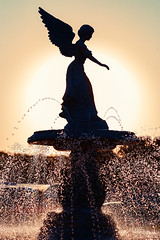 Angel of the Waters (www.toddklassy.com) Tags: park city travel sunset summer sunlight hot art water fountain beautiful weather silhouette statue vertical stone wisconsin architecture female angel backlight contrast outside droplets drops warm downtown day dusk scenic nobody landmark scene spray falling entertainment heat figure lakeshore leisure flowing backlit copyspace winged wi waterworks tranquil lakegeneva sprinkle angelofthewaters squirting rivierabeach colorimage walworthcounty lighthappiness thelegendofthefountain