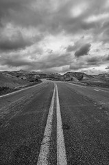 Road to Dillon Pass B&W (s.d.sea) Tags: road park trip travel vacation sky blackandwhite white black west nature lines yellow clouds landscape outdoors midwest moody angle pentax south wide perspective pass roadtrip national dillon winding badlands overlook dakota 15mm mounds