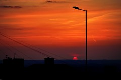 spot lamp (doods-on on weekends) Tags: roof sunset red chimney sky orange sun mountains clouds cloudy streetlamp