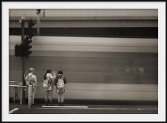 not a tram stop (Andrew C Wallace) Tags: city blur trafficlights sepia lensbaby ir crossing dof tram australia melbourne olympus victoria pedestrians infrared flindersstreetstation cbd schoolgirls stkildaroad tramstop tiltshift nd400 m43 nikon50mmf14 microfourthirds tilttransformer olympusomdem5