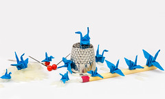 Is it smaller than a thimble? (docoverachiever) Tags: stilllife macro birds origami rice many object small pins cranes thimble tiny matchstick tabletop 63116