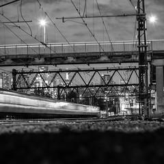 late night train (lucidddreamin') Tags: city longexposure railroad blackandwhite bw night train nightlights cloudy railway trains nighttime motionblur lighttrail