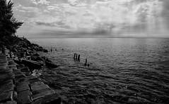 Beautiful Shoreline (mswan777) Tags: sunset sky sun lake seascape water clouds nikon rocks waves michigan shoreline scenic rays pilings 1855mm nikkor ansel expanse d5100