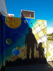 Going for a Space Walk (Steve Taylor (Photography)) Tags: blue boy shadow newzealand orange woman white streetart black art grass sunshine silhouette yellow wall lady digital stars graffiti toddler mural child walk space sunny nelson nz planet southisland weave solarsystem holdinghand
