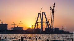 An amusing contrast at Dubai Marina beach ! (Alexandre Consten) Tags: sunset beach marina construction dubai factory jumeirah