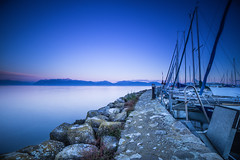 The Harbor with a view (Maximecreative) Tags: longexposure pink blue lake mountains alps water port boats concrete harbor pier twilight rocks waterfront calm lakeside serene bluehour sailboats leman f28 montblanc select morges voiliers 14mm samyang leefilters littlestopper