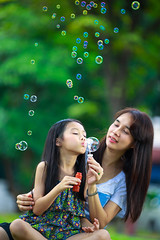Happy young mother and her daughter blowing soap bubbles in park (Patrick Foto ;)) Tags: park family summer portrait people woman baby playing cute green love nature girl beautiful grass childhood smiling lady female forest laughing children mom asian fun thailand outside happy kid spring soap child natural little outdoor background joy daughter young mother meadow adorable lifestyle happiness bubbles blowing blow thai bubble cheerful