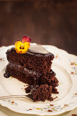 Piece of delicious rich chocolate cake decorated with a beautiful pansy flower (locrifa) Tags: party food brown white black flower cooking cakes floral beautiful up cake dark dessert colorful close dish sweet sauce chocolate background decoration pansy cream plate sugar petal mothers gourmet delicious eat slice pastry layer icing piece truffle celebrate mousse garnish decorated