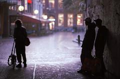 Arnhem in Rain (jonasfj) Tags: rain backlight waiting bicycle silhoutte carlzeiss 100 f2 library lights reflexions reflexion storytelling light 35mm thenetherlands netherlands holland nikonf4 f4 nikon arnhem kodakektar kodak ektar c41 street streetphotography film analog analogue 35mmfilm 100mm manualfocus