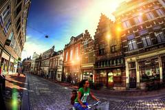 Here comes the sun (Frank//) Tags: street boy woman topf25 bike bicycle architecture female shopping topf50 topf75 europe child pavement dordrecht shops pm topf100 zuidholland nextime bui8ldings watmooi mrtungsten62 frankvandongen wwworvilnl