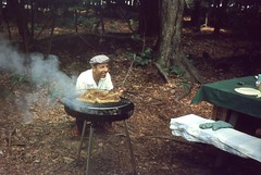 Barbecue Man (Alan Mays) Tags: old trees food men utensils cooking smiling portraits vintage clothing woods funny humorous photos smoke humor smiles hats steam grill ephemera clothes photographs tables grinning amusing slides kneeling cooks picnics picnictables transparencies foundphotos hunched barbecues huncheddown