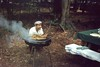 Barbecue Man (Alan Mays) Tags: ephemera slides transparencies photographs photos foundphotos guildcolor guildcolorprocessing portraits men clothing clothes hats barbecues grill utensils cooks cooking steam smoke food picnics picnictables tables trees woods kneeling hunched huncheddown smiles smiling grinning humor humorous funny amusing old vintage
