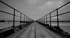 Pier through a lens. (wazimu0) Tags: wood winter sea blackandwhite bw cold canon pier vanishingpoint fishing walk decay south northsea railings planks blyth 2880mm rotton 5dmkii