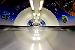 The London Eye (Mister T') Tags: city uk blue urban woman motion colour reflection london canon underground subway person lights movement space escalator tube sigma londoneye wideangle tunnel single 7d lone solitary 1020