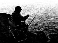 Fisherman at sunset (Lucio Busa) Tags: sea bw white fish black beach silhouette backlight relax fisherman mare calm cliffs e bianco nero spiaggia controluce pescatore scogli