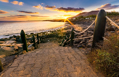 Playa Blanca (derekgordon1) Tags: sunset sea sky seascape beach water clouds fence outdoors volcano coast nikon rocks timber steps sigma lanzarote rope sunburst coastline f22 sunrays 1020 playablanca hdr waterscape d7100