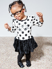 The Co-Conspiratorial Smile (Angela (Photography by Solaria)) Tags: two portrait black silly girl smile studio fun glasses toddler funny pretty dress dancing stock hipster dressup indoors trouble coconspirator modelreleased strobist