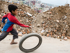 Spiderkid runs the wheel #2 (davdenic  in the sky ) Tags: nepal children game street
