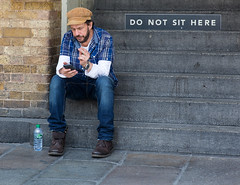 That means you,too... (James Thomas 10375) Tags: street white london up hat sign mobile shirt concrete concentration bottle shoes phone cigarette stonework steps jeans short roll sat relaxed volvic