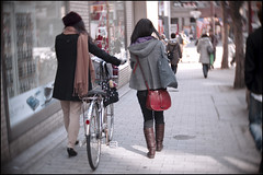 Walking with her bicycle and a friend (Eric Flexyourhead) Tags: street city girls urban woman blur girl bike bicycle japan walking japanese women candid kobe  kansai vignette hyogo sannomiya chuoku     kobeshi  olympusep1 slrmagic26mmf14toylens